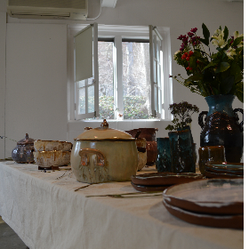 Image of ceramic food containers set up on a table with a vase of flowers